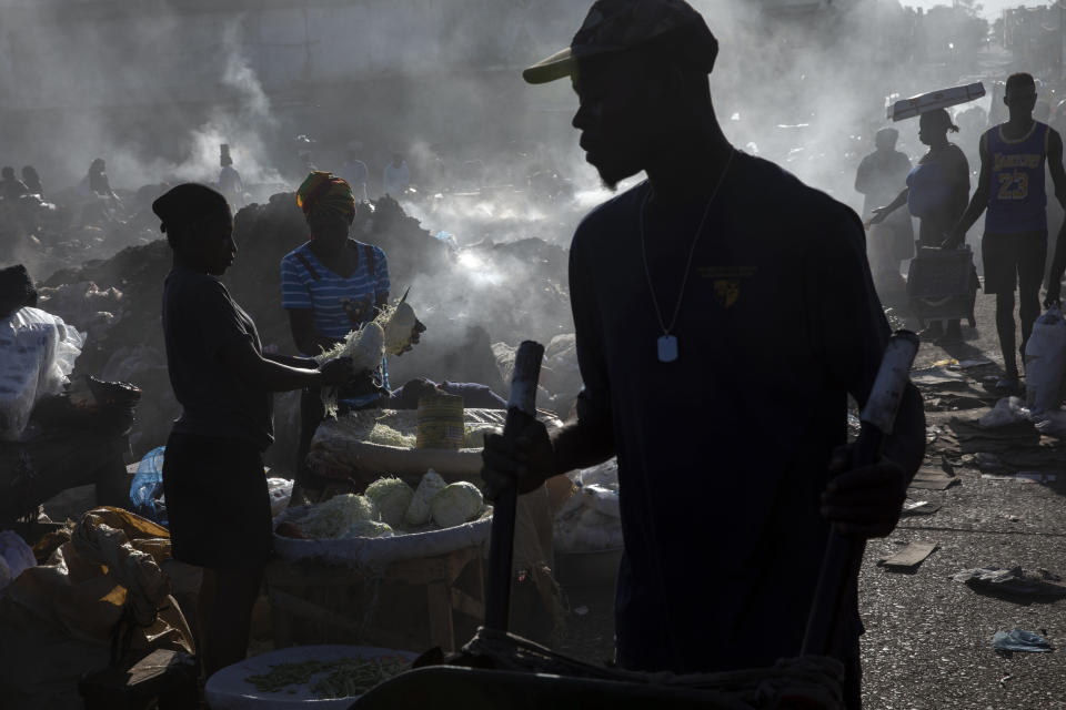 Vendors shred cabbage in the Croix des Bosalles market, in Port-au-Prince, Haiti, Monday, Sept. 13, 2021. The city's main food market extends from the southern entrance of the port to the parliament, on ground where enslaved people were sold before independence. To enter the market today, one must walk through a gang gauntlet. (AP Photo/Rodrigo Abd)