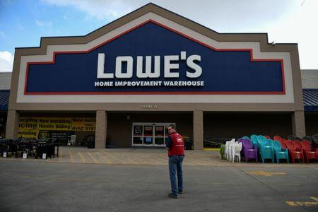 An employee stands outside a Lowe's home improvement chain in Austin, Texas