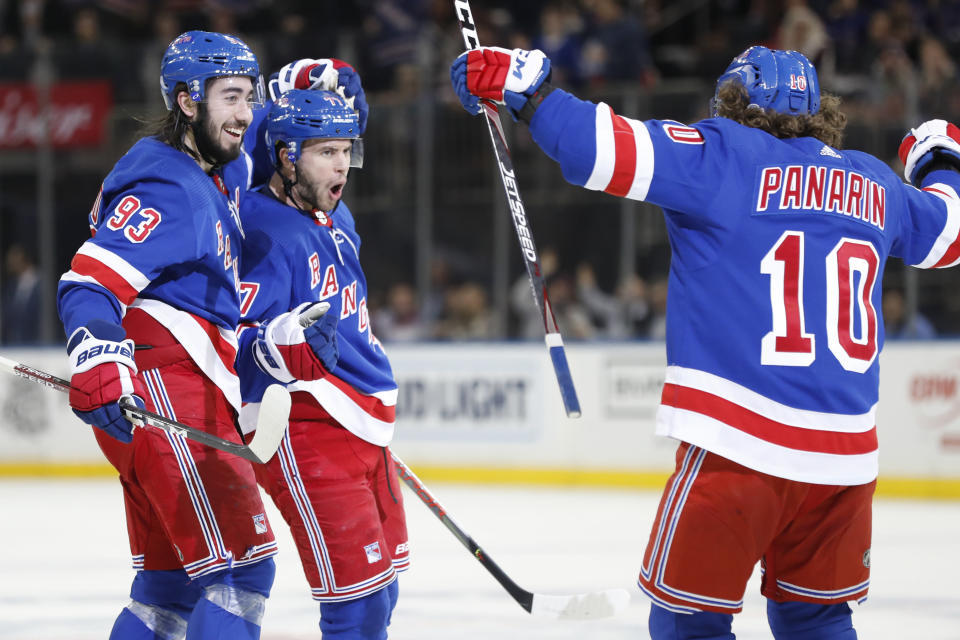New York Rangers center Mika Zibanejad (93), defenseman Tony DeAngelo (77) and and left wing Artemi Panarin (10) celebrate DeAngelo's hat trick during the second period of the team's NHL hockey game against the New Jersey Devils, Thursday, Jan. 9, 2020, in New York. (AP Photo/Kathy Willens)