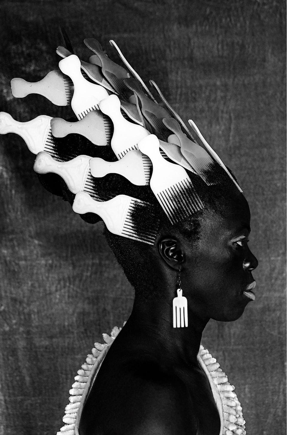 Person wearing afro combs in their hair and as earrings.