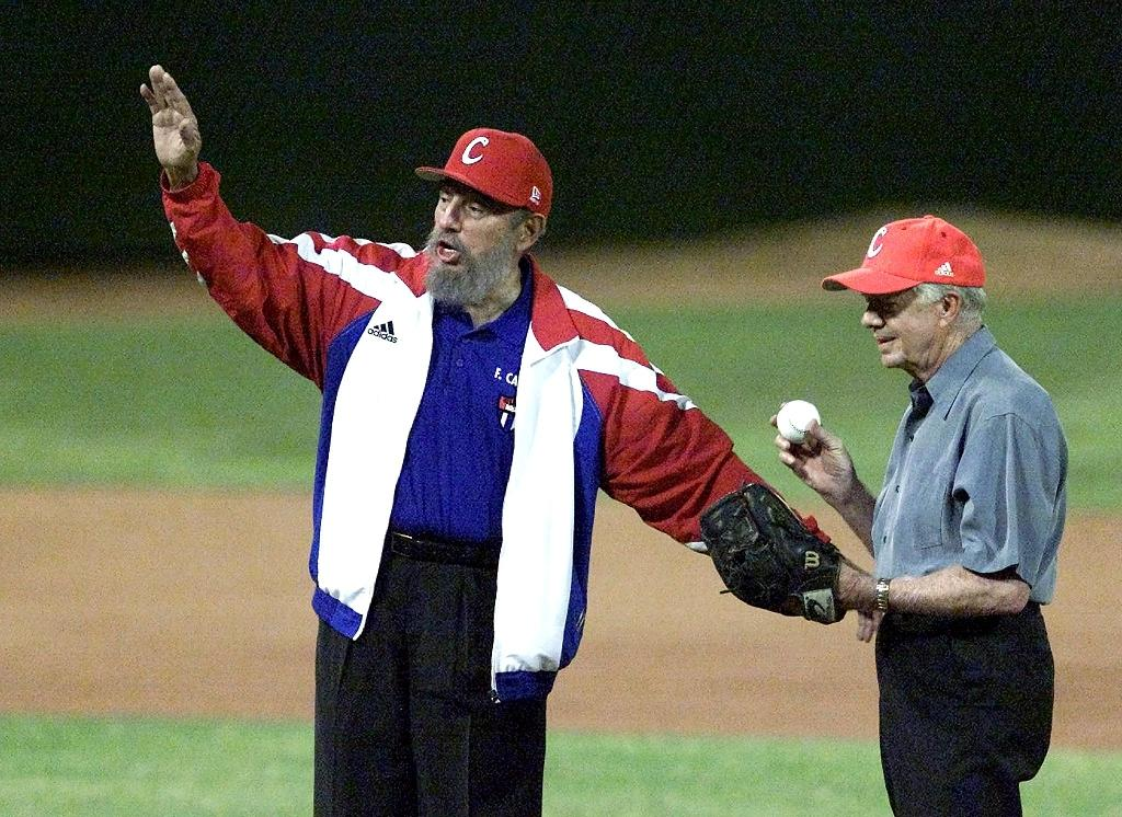 Cuban President Fidel Castro (L) calls for time as former US president Jimmy Carter prepares to throw the first pitch at a baseball game in Havana, in 2002 (AFP Photo/-, Adalberto Roque)