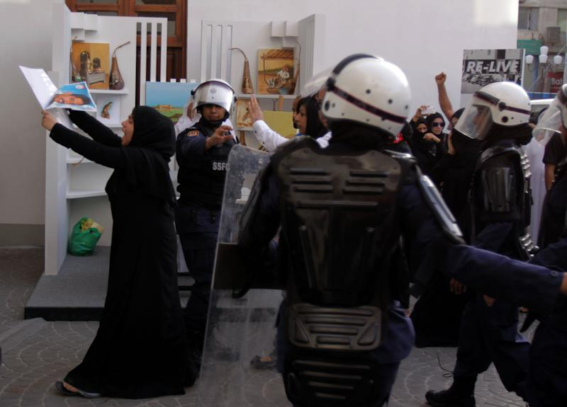 Bahraini anti-government protesters, led by an activist carrying a picture of jailed hunger striker Abdulhadi al-Khawaja, march Wednesday, April 18, 2012, through a tourist market in downtown Manama, Bahrain. Al-Khawaja's daughter, Zainab, also a prominent activist, follows her at center. Security forces fired stun grenades at the protesters who swarmed into a cultural exhibition for the Formula Bahrain One Grand Prix race, setting off street battles and sending visitors fleeing for cover. (AP Photo/Hasan Jamali)