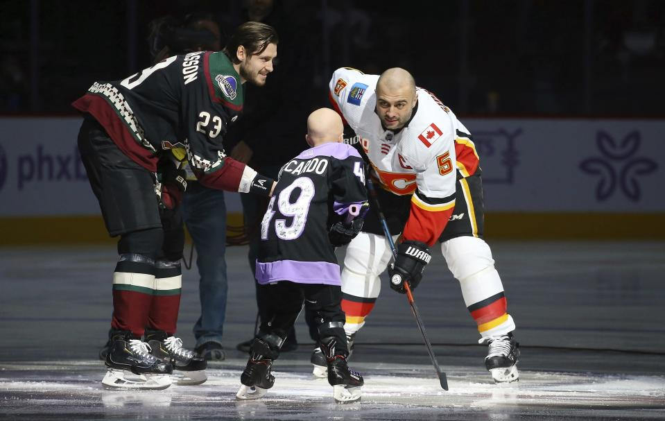 FILE - Arizona Coyotes' Oliver Ekman-Larsson (23) drops the puck in front of Leighton Accardo, middle, who is battling cancer, and Calgary Flames' Mark Giordano (5) during an NHL Fights Cancer puck drop ceremony prior to an NHL hockey game in Glendale, Ariz., in this Saturday, Nov. 16, 2019, file photo. Accardo's will to attack anything in her path, even terminal cancer, lifted an entire organization. The Arizona Coyotes will carry her spirit on by making her the first non-player, general manager or broadcaster to be inducted into an NHL team's ring of honor. (AP Photo/Ross D. Franklin, File)
