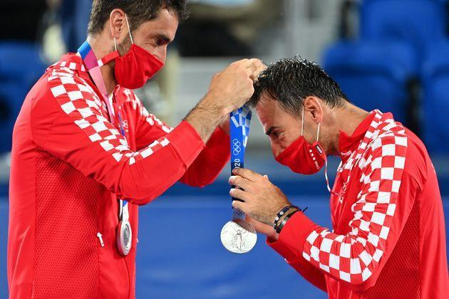 Silver medallist Marin Cilic of Croatia, left, gives Croatia's Ivan Dodig his silver medal on the podium during the men's doubles tennis ceremony at the Ariake Tennis Park in Tokyo on July 30. (Photo: VINCENZO PINTO via Getty Images)