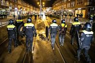 Police officers patrol the streets of Rotterdam a day after clashes with demonstrators protesting against new Covid-19 restrictions
