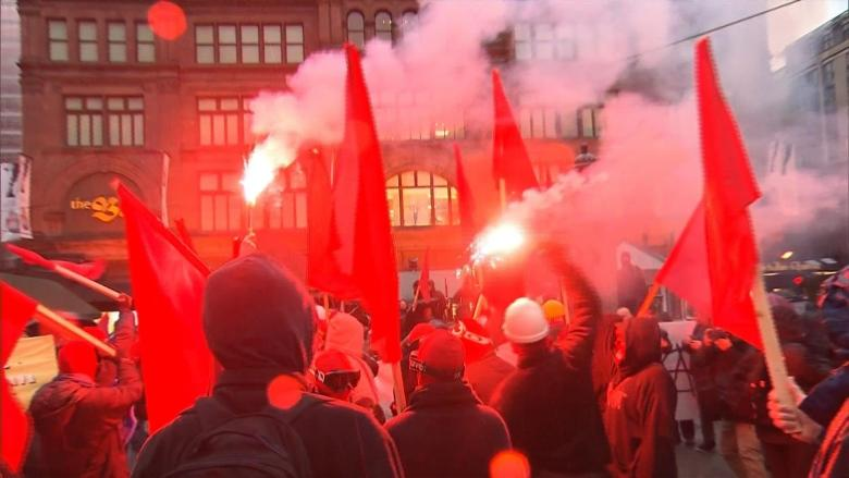Smoke bombs, smashed windows, 1 arrest at Montreal anti-capitalist march