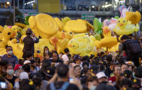 Inflatable yellow ducks, a recent symbol of the protest movement, are lifted over a crowd of anti-government protesters attending a rally Wednesday, Dec. 2, 2020, in Bangkok, Thailand. Thailand's highest court Wednesday acquitted Prime Minister Prayuth Chan-ocha of breaching ethics clauses in the country's constitution, allowing him to stay in his job. (AP Photo/Gemunu Amarasinghe)