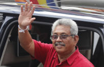 Sri Lankan President Gotabaya Rajapaksa waves as he leaves after casting his vote, outside a polling station in Colombo, Sri Lanka, Wednesday, Aug. 5, 2020. Sri Lankans started voting Wednesday to elect a new Parliament that is expected to give strong support to the powerful and popular Rajapaksa brothers. (AP Photo/Eranga Jayawardena)