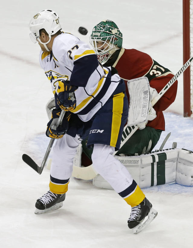 Nashville Predators' Patric Hornqvist, left, of Sweden tries to position himself for a pass as the puck sails past Minnesota Wild goalie Josh Harding in the first period of an NHL hockey game, Tuesday, Oct. 22, 2013, in St. Paul, Minn. (AP Photo/Jim Mone)