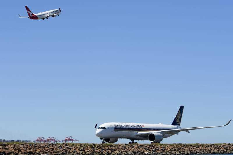 A Singapore Airlines Airbus A350 aircaft is seen arriving as a Qantas Boeing 737-800 departs, at Sydney International Airport.
