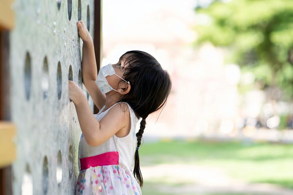 A child wearing a face mask looks up at a climbing wall.
