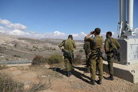 Israeli forces are seen near a border fence between the Israeli-occupied side of the Golan Heights and Syria