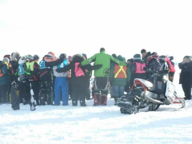 Racers gather for a group huddle at the Nattiq Frolics in 2014. A participant in a snowmobile race died Sunday after losing control during a race. (Nattiq Frolics/Facebook - image credit)