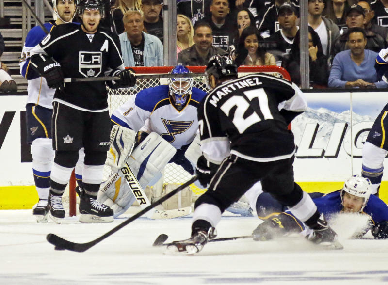Los Angeles Kings defenseman Alec Martinez (27) maneuvers for a shot on goal as St. Louis Blues goalie Brian Elliott (1) defends in the first period of Game 4 of the NHL Western Conference Stanley Cup hockey playoff series in Los Angeles, Monday, May 6, 2013. (AP Photo/Reed Saxon)