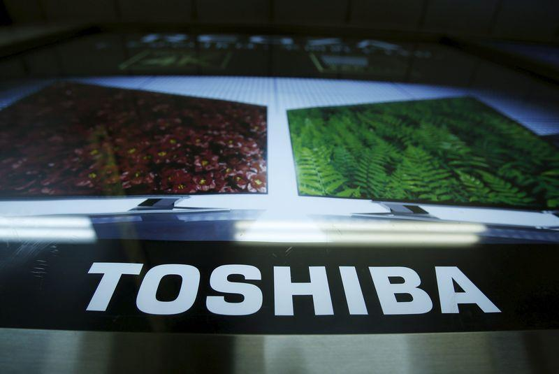 A logo of Toshiba Corp is seen next to an advertisement board for its Regza television in Tokyo