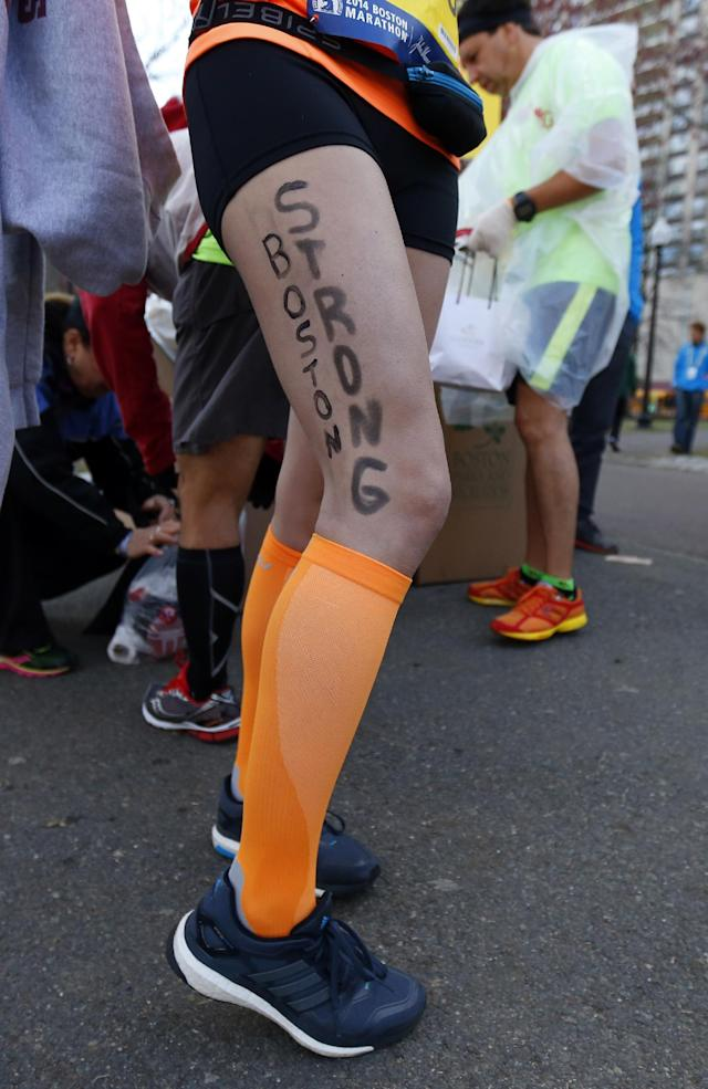 """Kimberley Garcia of Boston poses with the slogan """"Boston Strong"""" on her leg in Boston before boarding a bus to the starting line in Hopkinton, Mass., to compete in the 118th Boston Marathon Monday, April 21, 2014. (AP Photo/Matt Rourke)"""