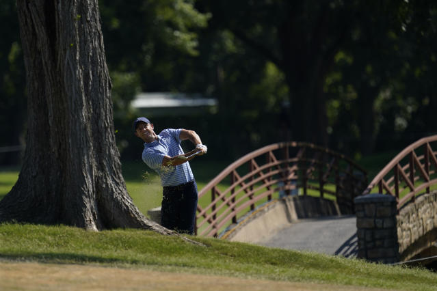 Rory McIlroy, of Northern Ireland, hits out of the rough on the 18th role during the third round of the Charles Schwab Challenge golf tournament at the Colonial Country Club in Fort Worth, Texas, Saturday, June 13, 2020. (AP Photo/David J. Phillip)