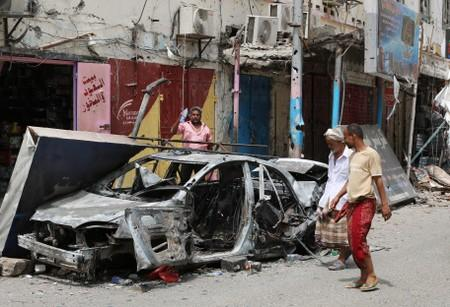People check cars that were burned during clashes in Aden