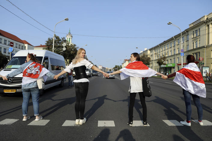 Women cover themselves with old Belarusian national flags as they block a road, during an opposition rally to protest the official presidential election results in Minsk, Belarus, Saturday, Sept. 12, 2020. Daily protests calling for the authoritarian president's resignation are now in their second month and opposition determination appears strong despite the detention of protest leaders. (AP Photo)