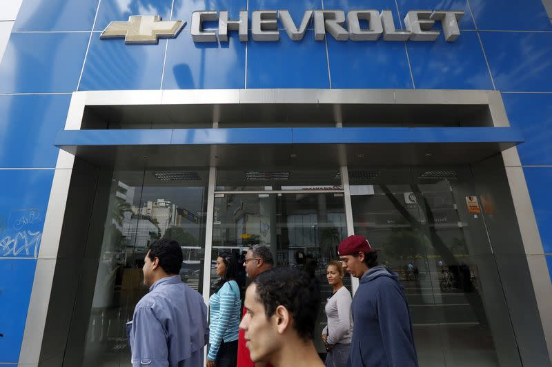 People walk past a closed Chevrolet branch in Caracas
