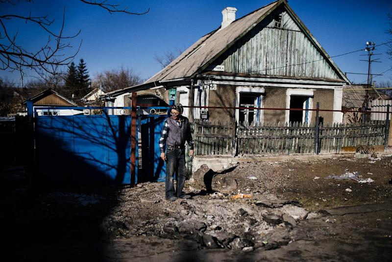 A Ukrainian resident inspects a crater following fresh shelling of the Kuybeshevski area of Donetsk, on November 6, 2014 (AFP Photo/Dimitar Dilkoff)