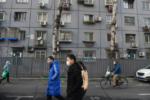 Beijing residents, wearing face masks, walk past a residential building -- the new-coronavirus death toll exceeds that of the 774 killed worldwide by SARS