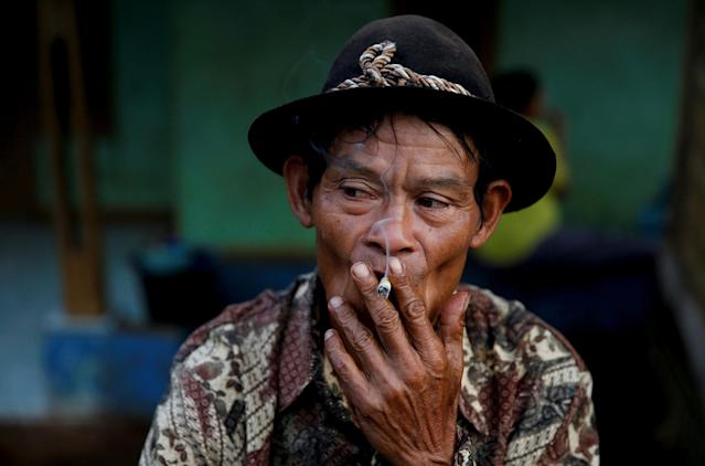 <p>A street vendor smokes a cigarette as he waits for customers in Cikawao village of Majalaya, West Java province, Indonesia, Oct. 12, 2017. (Photo: Beawiharta/Reuters) </p>