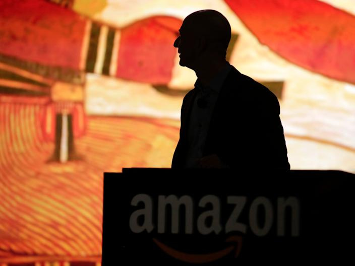 Amazon CEO Jeff Bezos is silhouetted during a presentation of his company's new Fire smartphone at a news conference in Seattle, Washington June 18, 2014.