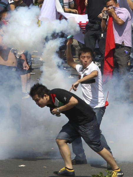 A Chinese demonstrator throws a teargas canister back to the riot policemen during a protest against Japan in Shenzhen, China Sunday, Sept. 16, 2012. Protesters in China began another day of demonstrations against Japan, after protests over disputed islands spread across numerous cities and at times turned violent. (AP Photo/Apple Daily) HONG KONG OUT, TAIWAN OUT, NO SALES
