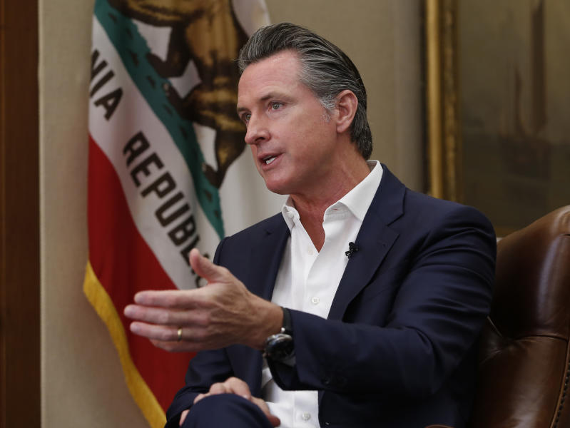 FILE - In this Oct. 8, 2019, file photo, California Gov. Gavin Newsom gestures during an interview in Sacramento, Calif. The Democrats who rule California took on homegrown tech giants Uber and Lyft over their work force, convinced some of the world's biggest automakers to buck the president on fuel emissions and passed a law that could change college sports. On issues big and small, hotels soon will be forbidden from providing guests with little plastic shampoo bottles, California this year has marched farther left and tried to pull the rest of the country with it. (AP Photo/Rich Pedroncelli, File)