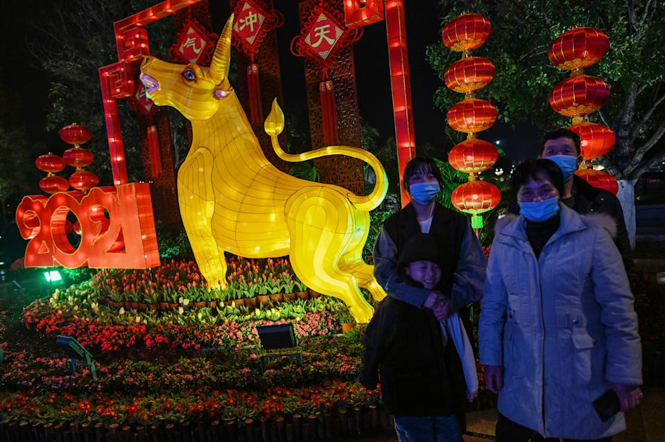 A family wearing face masks pose for pictures next to the figure of an ox in Wuhan in China's central Hubei province on February 10, 2021, ahead of the biggest holiday of the year, the Lunar New Year, which ushers in the Year of the Ox on February 12. (Photo by Hector RETAMAL / AFP) (Photo by HECTOR RETAMAL/AFP via Getty Images)