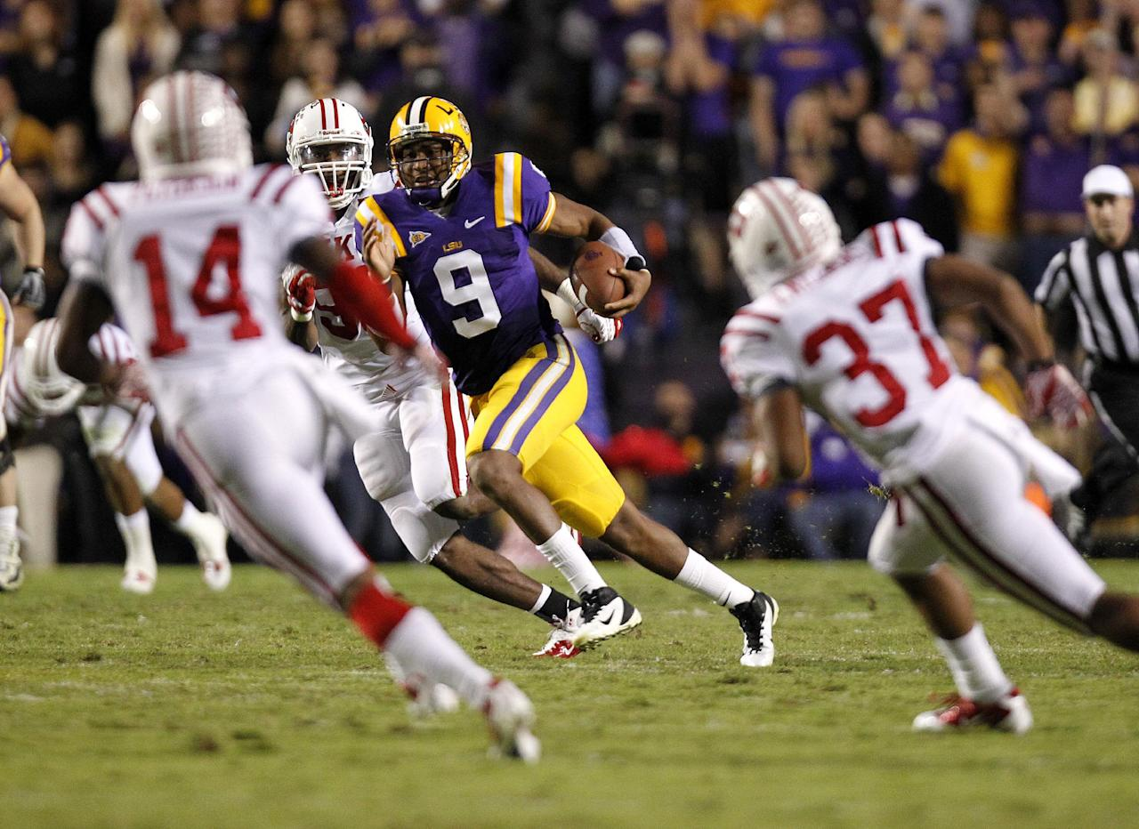 LSU quarterback Jordan Jefferson (9) rushes as Western Kentucky defensive back Kareem Peterson (14) and defensive back Vince Williams (37) converge during the second quarter of their NCAA college football game in Baton Rouge, La., on Saturday, Nov. 12, 2011. (AP Photo/Gerald Herbert)