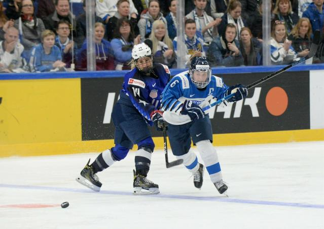 Brianna Decker, left, of the United States and Jenni Hiirikoski of Finland vie for the puck during the IIHF Women's Ice Hockey World Championships final match between the United States and Finland in Espoo, Finland, Sunday, April 14, 2019. (Mikko Stig/Lehtikuva via AP)
