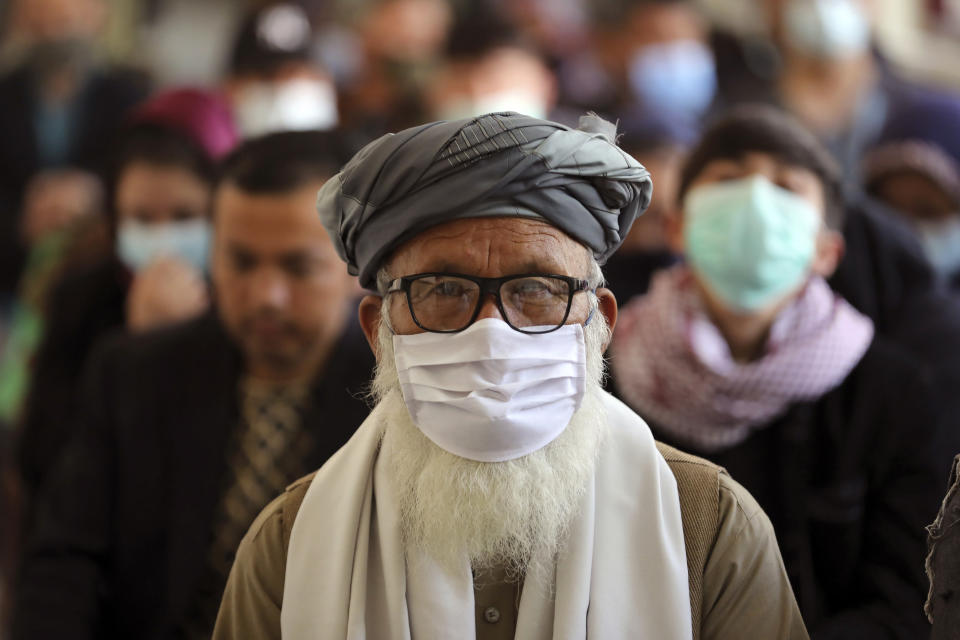 Afghan people wait to receive the Indian version of the AstraZeneca coronavirus vaccine at a hospital in Kabul, Afghanistan, Tuesday, May 11, 2021. (AP Photo/Rahmat Gul)