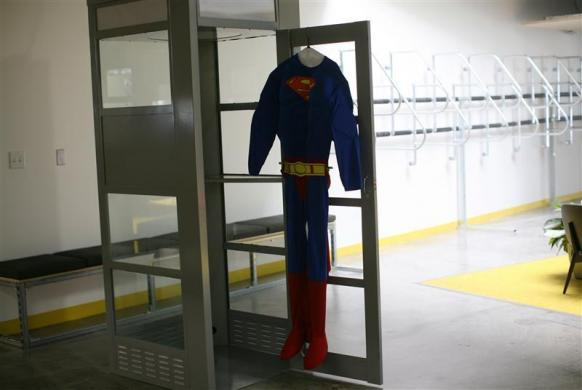 A superman costume hangs at a telephone booth for private cell phone discussions at the new headquarters of Facebook in Menlo Park, California January 11, 2012.