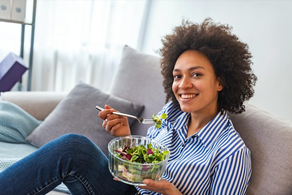 american woman eating vegetable salad at home