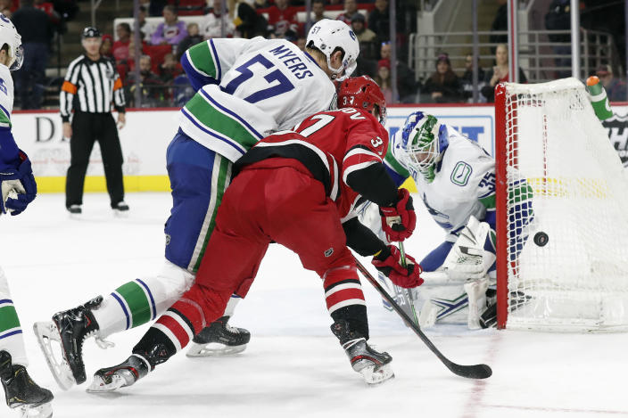 Carolina Hurricanes right wing Andrei Svechnikov (37), of Russia, tries to score while Vancouver Canucks defenseman Tyler Myers (57) and goaltender Thatcher Demko (35) defend during the second period of an NHL hockey game in Raleigh, N.C., Sunday, Feb. 2, 2020. (AP Photo/Gerry Broome)