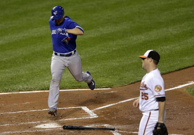 Toronto Blue Jays' Josh Thole, left, crosses home plate in front of Baltimore Orioles starting pitcher Bud Norris for a run on a single hit by Jose Reyes in the second inning of a baseball game on Wednesday, Sept. 25, 2013, in Baltimore. (AP Photo/Patrick Semansky)