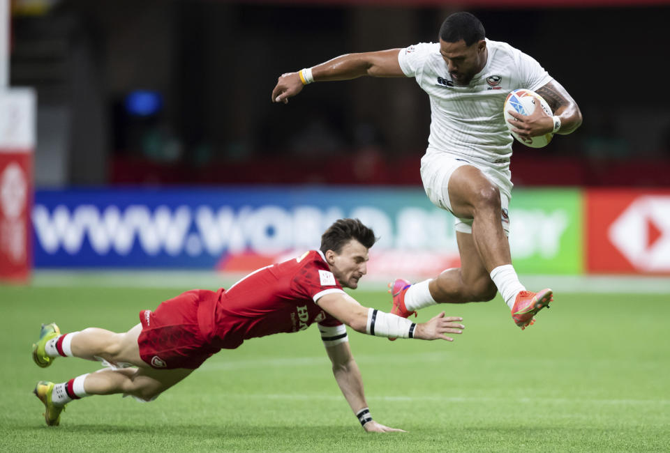 United States' Martin Iosefo, right, leaps past Canada's Andrew Coe and runs the ball for a try during an HSBC Canada Sevens rugby game in Vancouver, British Columbia, Saturday, Sept. 18, 2021. (Darryl Dyck/The Canadian Press via AP)