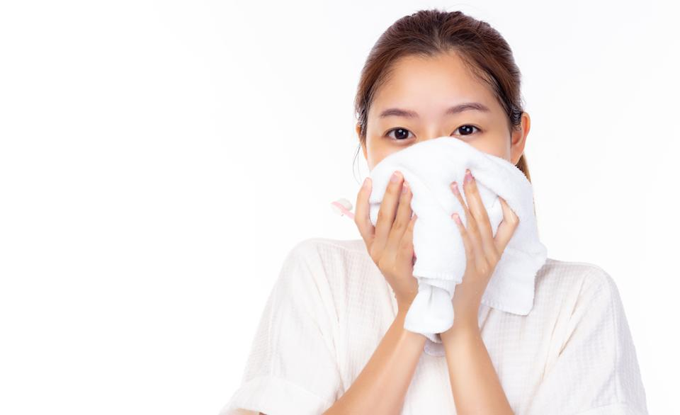 Young asian woman wiping face with towel in bathroom, white background. Cleaning face skin. Portrait beautiful smiling girl holding white towel near beauty facial skin after washing face, copy space