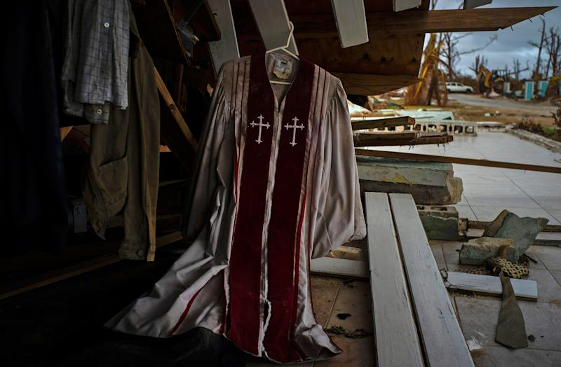 Priest's mass vestments hang in the rubble of a destroyed house by Hurricane Dorian in Pelican Point, Grand Bahama, Bahamas, Sept. 14, 2019. | Ramon Espinosa—AP
