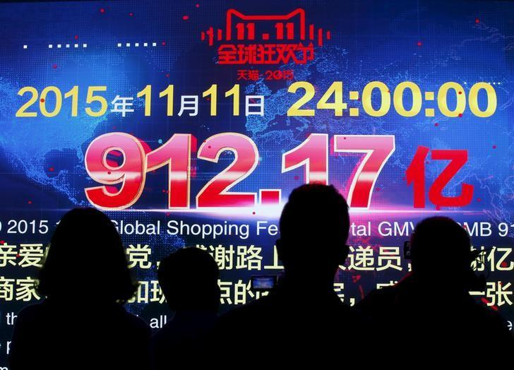 Journalists look at a screen showing total value of goods transacted at Alibaba Group's 11.11 Global shopping festival in Beijing
