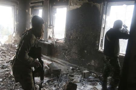 Rebel fighters take positions inside a damaged building during clashes with forces loyal to Syria's President Bashar al-Assad who are stationed in Aleppo's historic citadel December 7, 2014. REUTERS/Abdalrhman Ismail