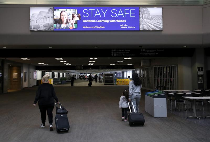 SAN FRANCISCO, CALIFORNIA - APRIL 12: Passengers walk through the United Airlines terminal at San Francisco International Airport on April 12, 2020 in San Francisco, California. San Francisco International Airport has a seen a huge decline in daily flights since the coronavirus shelter in place. United Airlines, the airport's largest carrier with the most daily flights with 290 flights per day before the start of the COVID-19 pandemic, has reduced their daily flights to 50 per day. (Photo by Justin Sullivan/Getty Images)