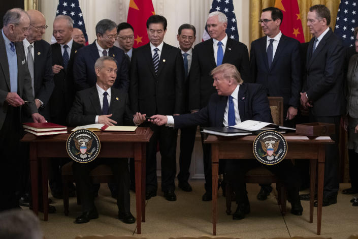 """In this Jan. 15, 2020, photo, President Donald Trump hands a pen to Chinese Vice Premier Liu He after signing """"phase one"""" of a US China trade agreement, in the East Room of the White House in Washington. (AP Photo/ Evan Vucci)"""
