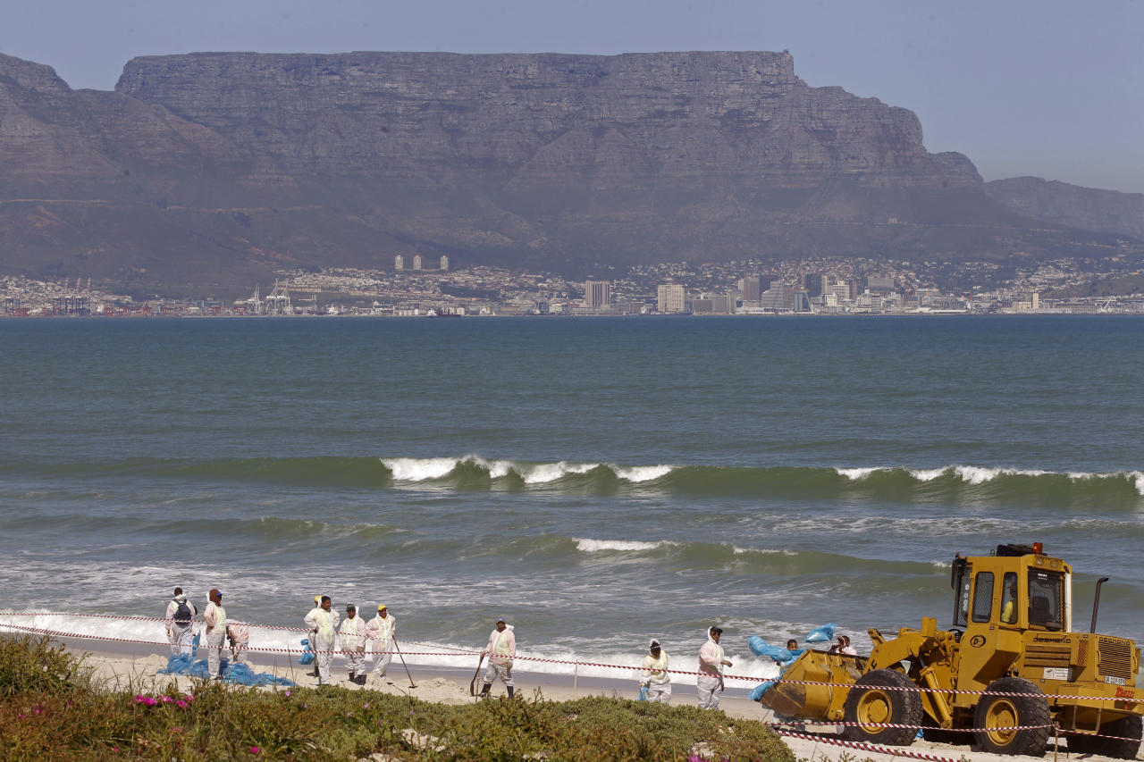 Workers clean a beach area after oil leaked from a Turkish owned vessel, unseen, with Table Mountain in background, that ran aground in Bloubergstrand, South Africa, Monday, Sept 5, 2011. The Turkish-owned vessel ran aground in 2009, it was carrying fuel, oil and coal at the time. (AP Photo/Schalk van Zuydam)