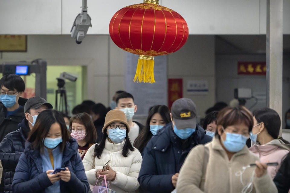 Commuters wearing face masks to protect against the spread of the coronavirus walk through turnstiles in a subway station during the evening rush hour in Beijing, Friday, Feb. 26, 2021. China has been regularly reporting no locally transmitted cases of COVID-19 as it works to maintain control of the pandemic within its borders. (AP Photo/Mark Schiefelbein)