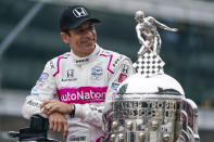 Helio Castroneves of Brazil, winner of the 2021 Indianapolis 500 auto race, poses during the traditional winners photo session at the Indianapolis Motor Speedway in Indianapolis, Monday, May 31, 2021. (AP Photo/Michael Conroy)