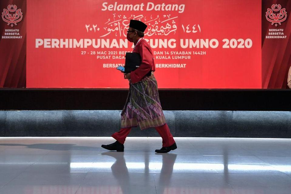 An Umno member arrives for the party's 2020 general assembly in Kuala Lumpur March 28, 2021. ― Bernama pic