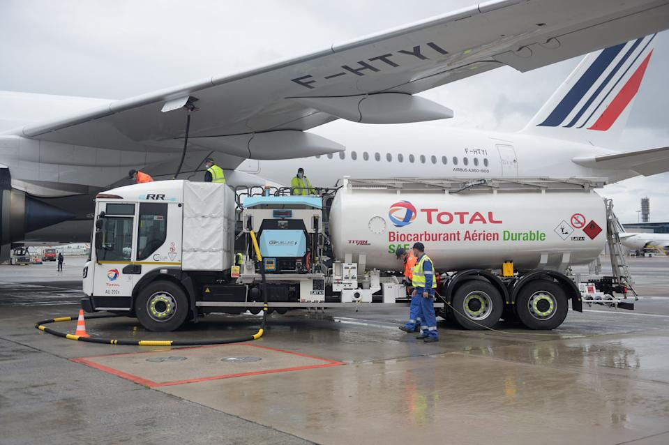 Staff members refuel an Airbus A350-900, the first Air France jet long-haul aircraft fuelled with sustainable aviation fuel (SAF) produced by French energy group Total at Roissy airport on May 18, 2021. (Photo by Eric PIERMONT / AFP) (Photo by ERIC PIERMONT/AFP via Getty Images)